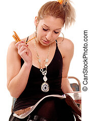 At leisure - Young woman sitting and reading newspaper and...