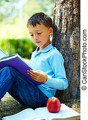 At leisure - Portrait of smart boy in the park and reading...