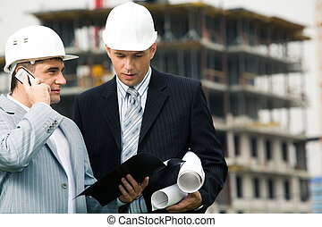 Portrait of two engineers interacting at building site outdoor