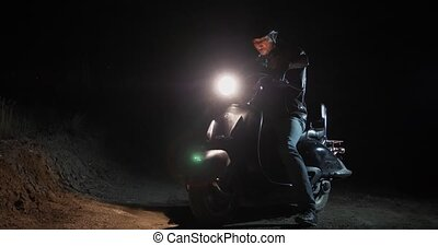 At night a man on a moped stopped in the middle of a country...