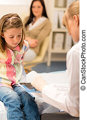 At pediatrician office girl look medical document