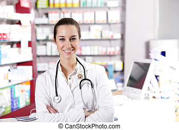 At pharmacy. A smiling young woman pharmacist with...