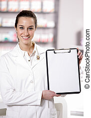 At pharmacy. Photo of an attractive young woman pharmacist with a clipboard. copy space