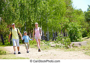 At summer - Portrait of three family members walking down...
