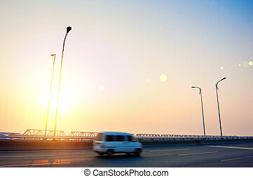 At sunset, a car on the highway
