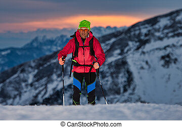 At sunset a ski touring uphill on the Alps