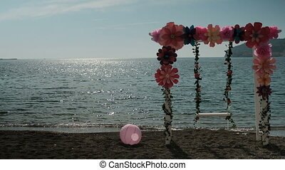 At sunset at the shore stand a swing with decorations and a ball.