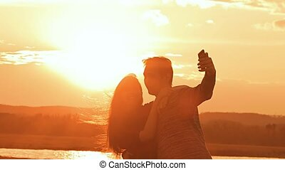 at sunset couple takes selfie slow motion video