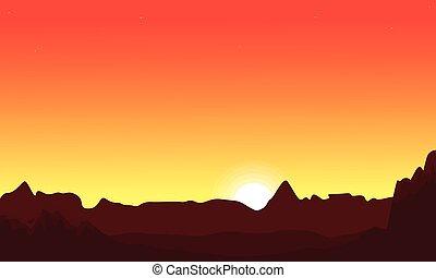 At sunset desert landscape with orange sky