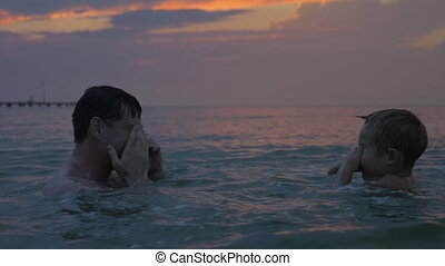 At sunset father with son swimming in sea of city Perea, Greece