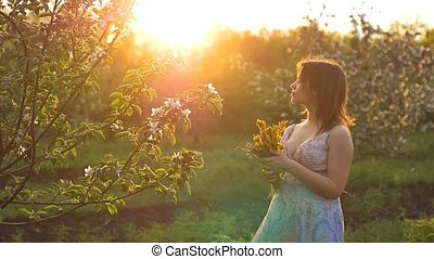 sunset in the background cute girl in the flowered garden with a bouquet in the hands of the slow motion video