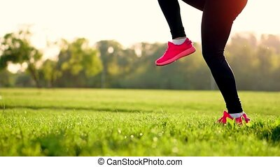 At sunset in a field of sporty girl on the grass in a white top and pink sneakers makes the warm-up run before lifting hips. Sport. close up. Grass sneakers