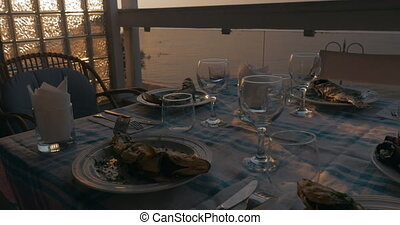 At sunset in city of Perea, Greece, dinner table served with cooked fish