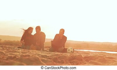 man talking on the phone woman with a guy sitting in the sand slow motion video