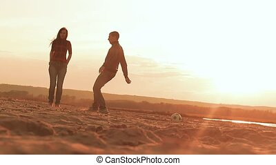 at sunset man chasing a soccer ball on the beach slow motion video