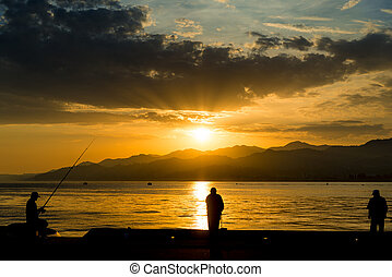 At sunset, men with fishing rods fish on the pier