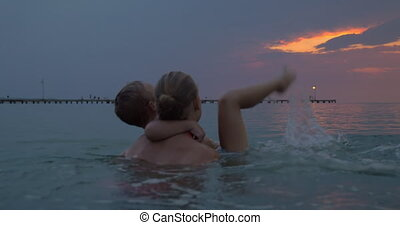 At sunset mother with son swimming in sea of city Perea, Greece