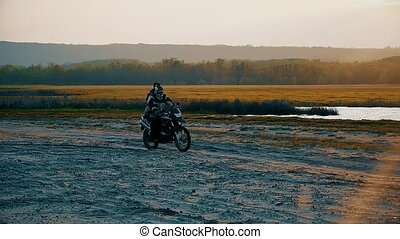 at sunset near the lake motorcyclist rides slow motion video...