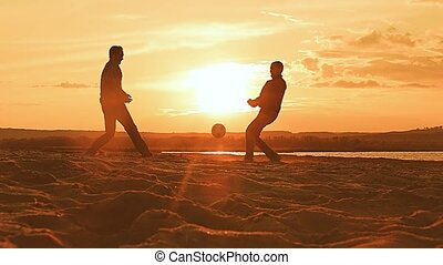 at sunset the men throw up the ball up the slow-motion video...
