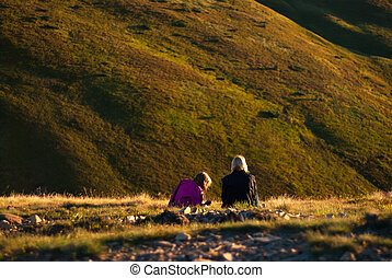 at sunset the two girls sitting in the mountains