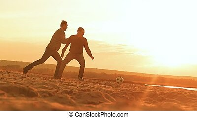 at sunset the two men playing ball, slow motion video