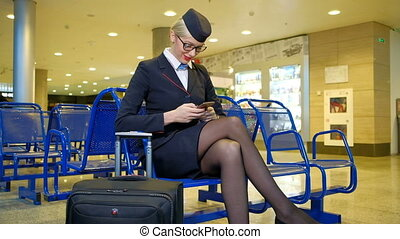 At the airport sits stewardess with luggage and holding smartphone.