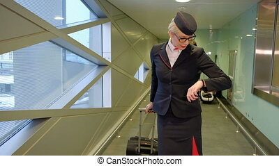 At the airport stewardess with suitcase goes and looks at his watch.
