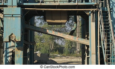 At the asphalt plant, an iron trolley approaches the storage...