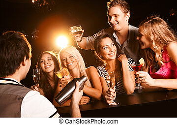 Photo of joyful friends in the bar communicating with each other