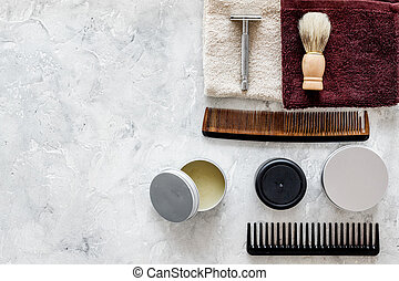 At the barbershop. Razors, shaving brush, comb, wax, towel on grey background top view copyspace