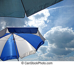 At the Beach - Relaxing under sun umbrellas on a cloudy...