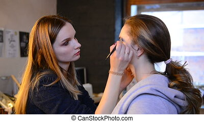 At the beauty salon female makeup brush does makeup on the model face.