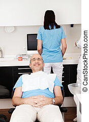 At the dentist - Cheerful patient in the dentist's chair in...