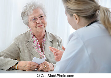 at the doctors office - doctor explaining diagnosis to his...