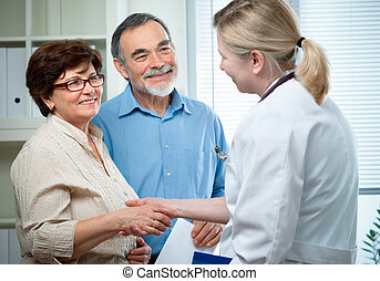 at the doctors office - senior couple visiting a doctor