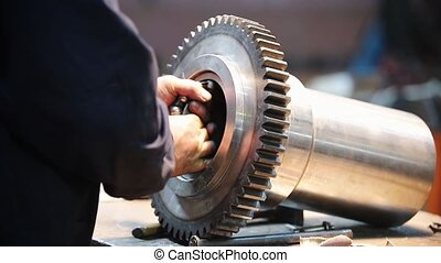At the factory, a man installs a bearing in gear - Work on...