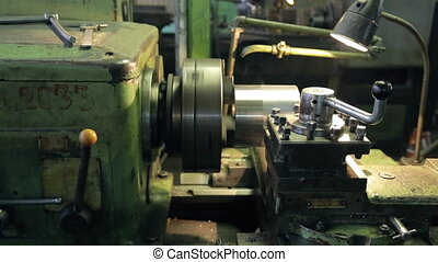At the factory old horizontal lathe aligns layer of metal parts.
