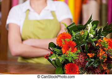 At the flower shop. Cropped image of young blond hair woman in apron keeping arms crossed while bunch on flowers laying o foreground