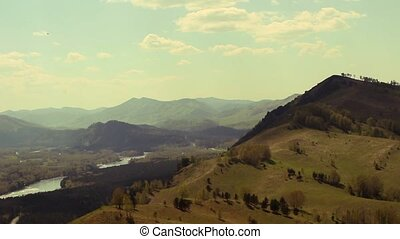 At the foot of the mountains of Gorny Altai floating clouds, casting a shadow on the green hill