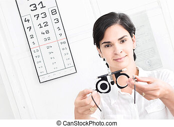 At the Optician - Young female optometrist with an universal...