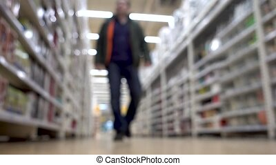At the Supermarket: Man walking in supermarket shop. Blurred...