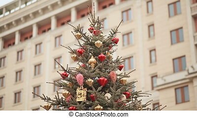 At the top of the Christmas tree, sparkling lights and beautiful Christmas decorations against the backdrop of a large building. New Year theme.