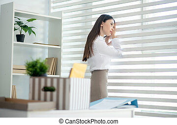 Young brunette female looking into the window, her box with personal stuff standing on desk