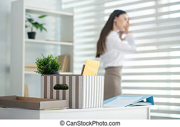 Young brunette female standing at the window, her box with personal stuff standing on desk