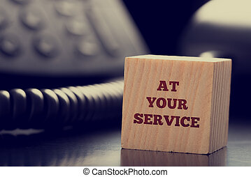 At Your Service written on a wooden cube in front of a...