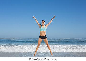 ataque, mujer, saltar, en la playa, con, brazos hacia fuera