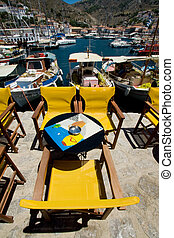 athena setaing - greek island cafe with yellow chairs