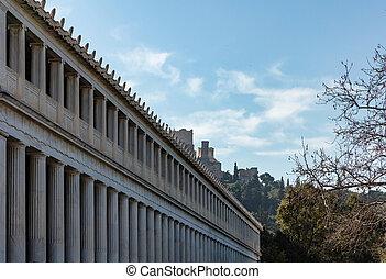Athens Greece. Attalus stoa facade columns, Acropolis rock background, blue sky, sunny day. .