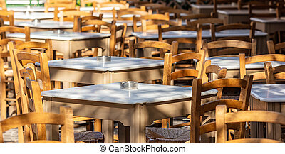 Athens, Greece. Greek tavern empty tables and chairs at...