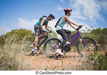athlétique, couple, montagne faisant vélo